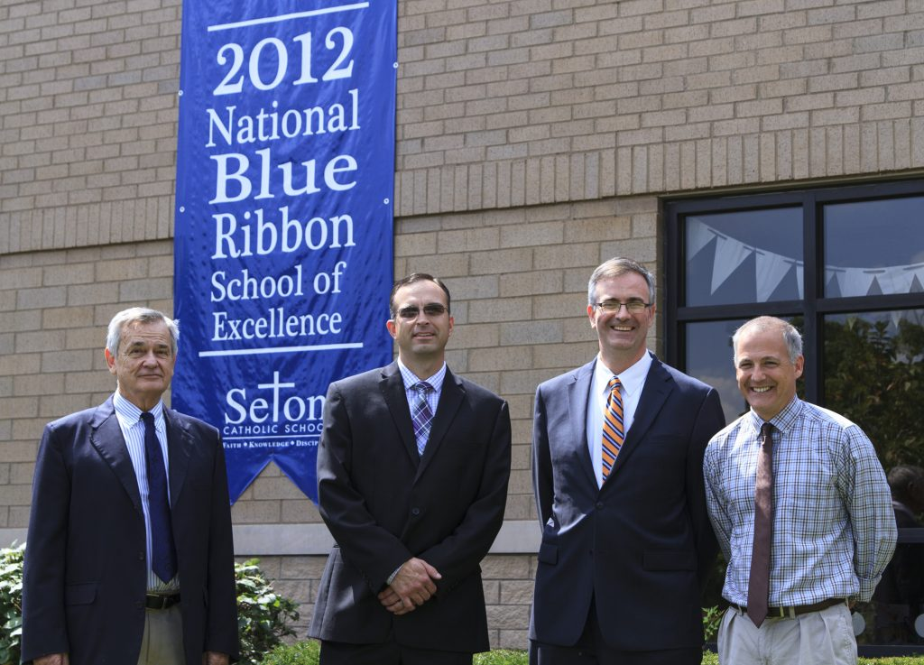 Left to right, Diocese of Lexington interim superintendent of schools George Pressey, assistant superintendent Jeremy Hughes, NCEA president and CEO Dr. Tom Burnford, and Seton principal Gene Cahill in front of Seton Catholic School in Lexington during Burnford's tour of diocesan schools. CR photo: Skip Olson
